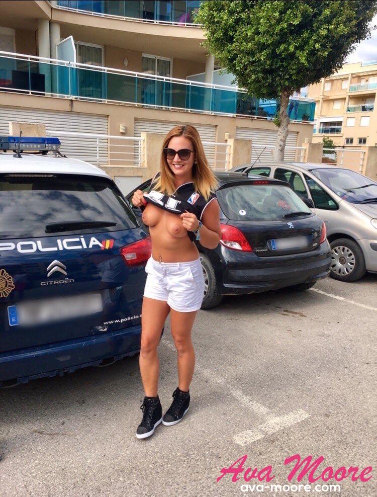 Devant une voiture de flic, Ava Moore montre ses boobs